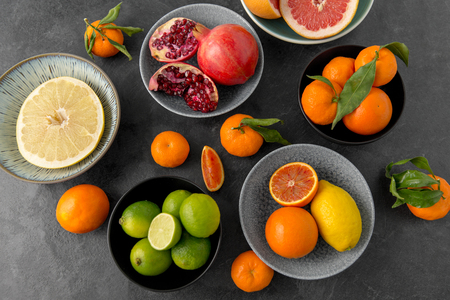 close up of citrus in bowls fruits on stone table Stock Photo