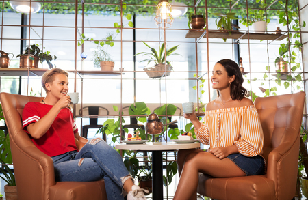 female friends drinking tea and talking at cafe