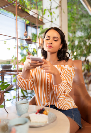 woman photographing food by smartphone at cafe