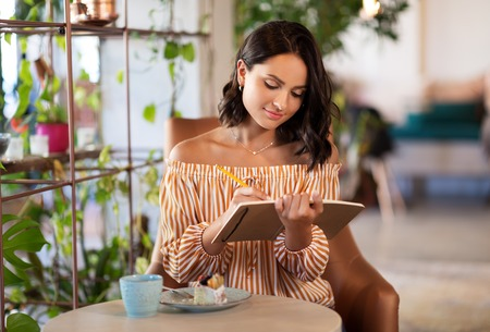 happy woman with notebook at coffee shop or cafe Stock Photo