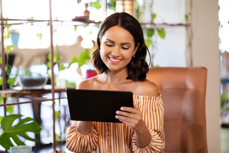 happy woman with tablet pc at cafe or coffee shop