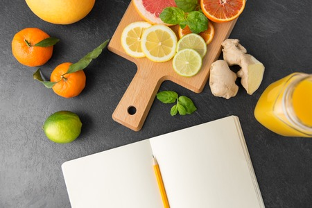 close up of fruits and notebook on slate table top Stock Photo