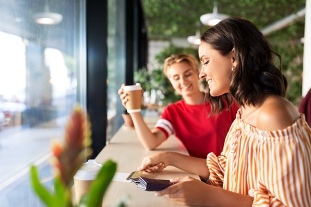 female friends paying by credit card at cafe