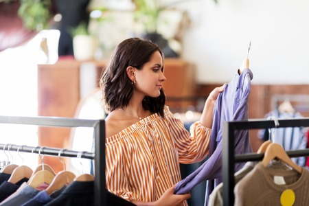 woman choosing clothes at vintage clothing store Stock Photo