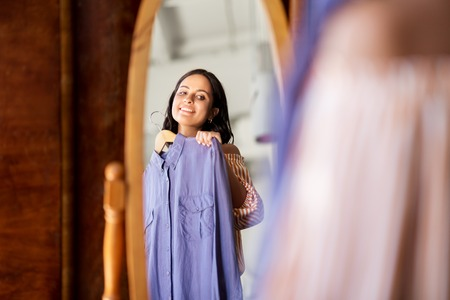 woman with dress at vintage clothing store mirror