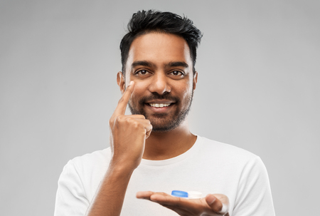 young indian man applying contact lenses