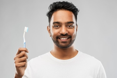 indian man with toothbrush over gray background Stock Photo