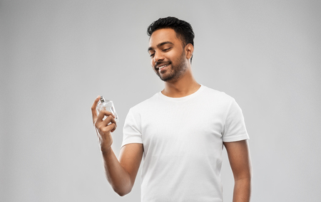 male perfumery, grooming and people concept - happy smiling young indian man with perfume over gray background Stock Photo