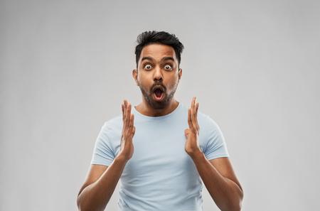 Concepto de emoción, expresión y personas - hombre asustado en camiseta sobre fondo gris