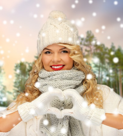 happy woman in winter clothes showing hand heart