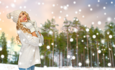 happy woman in hat and scarf over winter forest Stockfoto