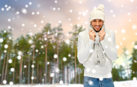 smiling man in hat and scarf over winter forest
