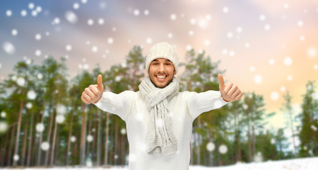 smiling man showing thumbs up over winter forest