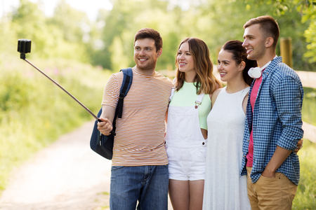 friends take picture by smartphone on selfie stick