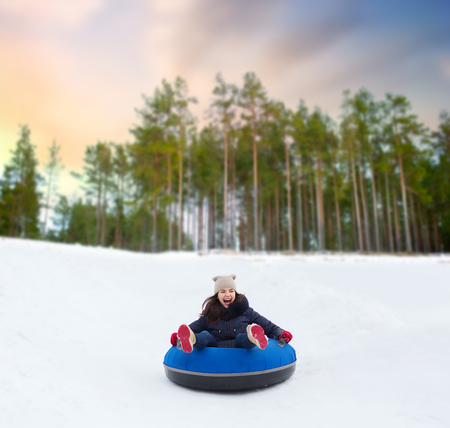 happy teenage girl sliding down hill on snow tube Reklamní fotografie - 111438442