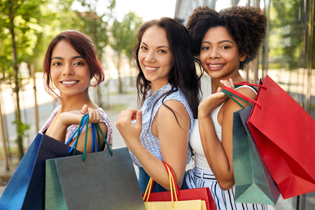 happy women with shopping bags in city Фото со стока