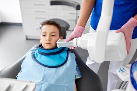 dentist making x-ray of kid teeth at dental clinic