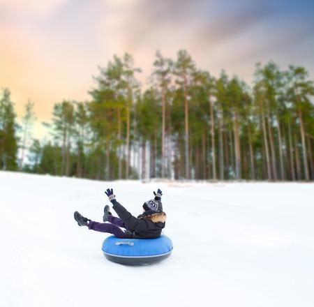 happy young man sliding down hill on snow tube Reklamní fotografie