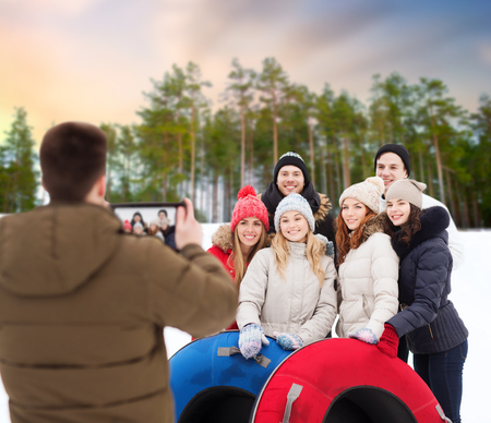 friends with snow tubes taking photo by tablet pc