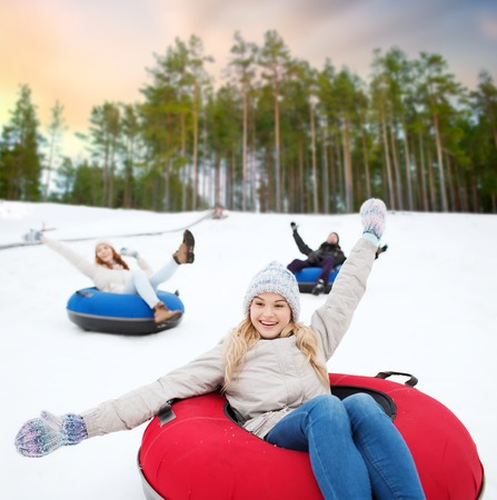 happy friends sliding down hill on snow tubes Stock Photo