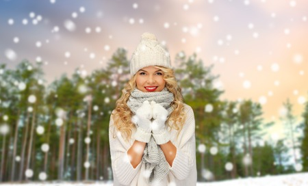 happy woman in hat and scarf over winter forest Stockfoto - 111560126