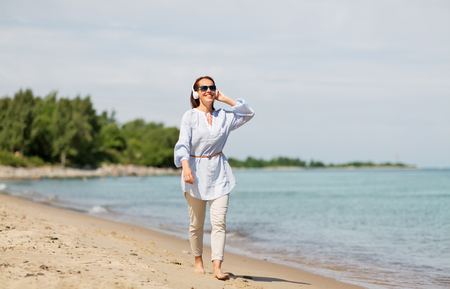 woman with headphones walking along summer beach 写真素材 - 111561846