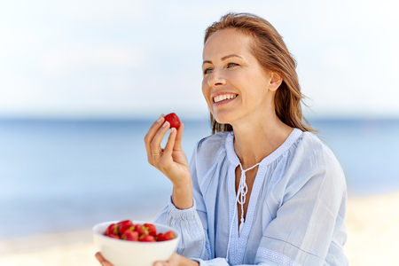 Mujer feliz comiendo fresas en la playa de verano Foto de archivo