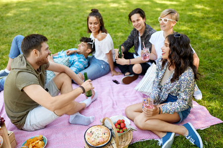 happy friends with drinks at picnic in summer park Banco de Imagens