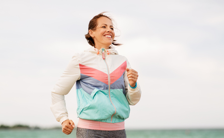 smiling woman running along beach