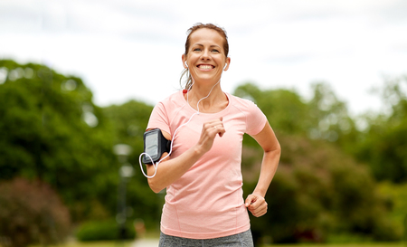 woman with earphones add armband jogging at park