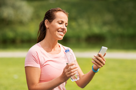 woman with smartphone drinking water in park