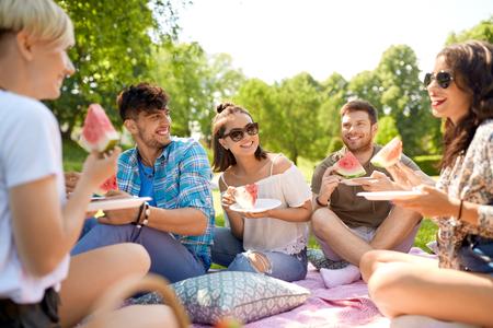 happy friends eating watermelon at summer picnic Фото со стока