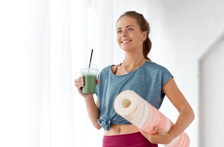 woman with cup of smoothie and mat at yoga studio