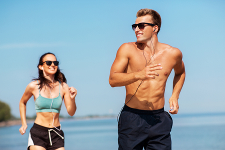 couple with earphones running along on beach