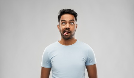 indian man making faces and showing his tongue Stock Photo
