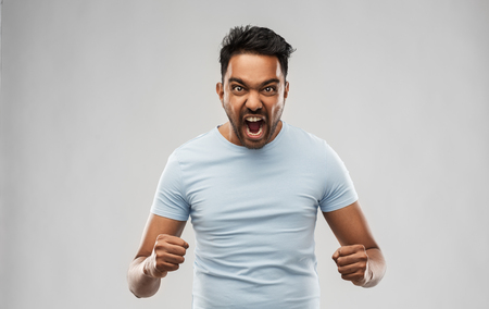 angry indian man screaming over grey background Archivio Fotografico