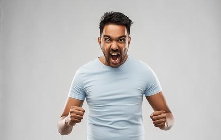 uomo indiano arrabbiato che urla su sfondo grigio Archivio Fotografico