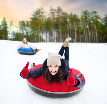 happy teenage girl sliding down hill on snow tube Stockfoto