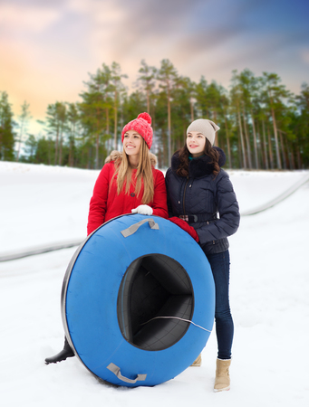 happy teenage girls with snow tubes in winter
