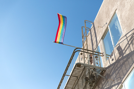 pride rainbow flag waving on building balcony