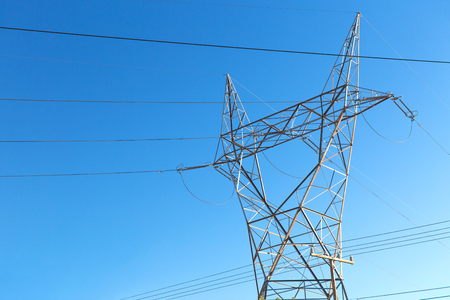 transmission tower and power line over blue sky