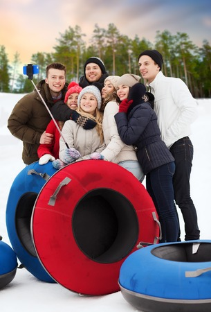 friends with snow tubes taking selfie in winter