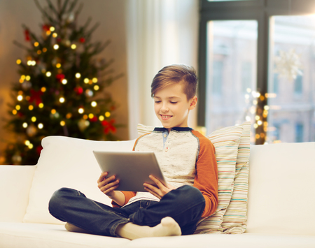 boy with tablet computer on christmas at home