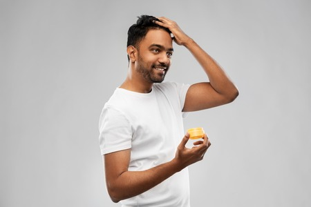 indian man applying hair wax or styling gel
