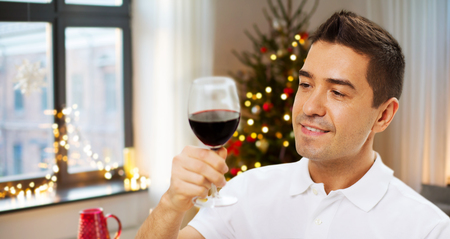 happy man drinking red wine at home on christmas