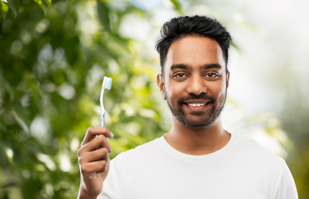 indian man with toothbrush over natural background