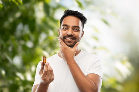 indian man applying natural grooming oil to beard