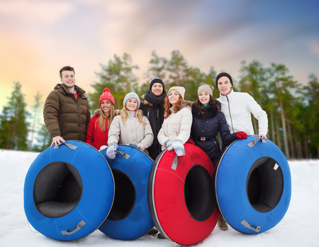 happy friends with snow tubes outdoors in winter