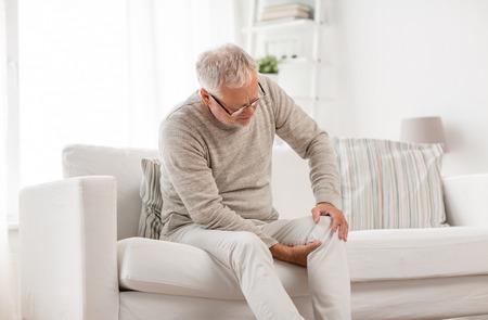älterer Mann, der zu Hause unter Knieschmerzen leidet