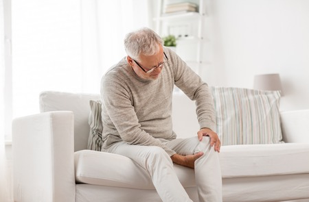 senior man suffering from knee ache at home Stockfoto